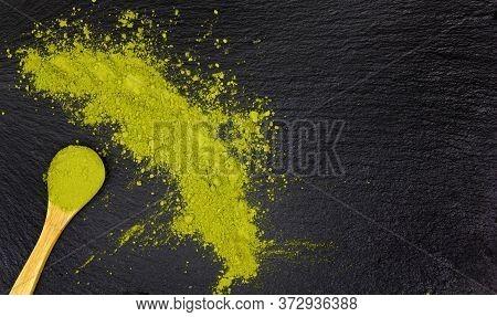 Heap Of Green Detox Superfood Powder (matcha Green Tea Or Spirulina Powder) With A Spoon On Dark Bac