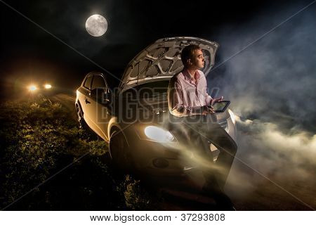 Young man exploring the map on tablet pc computer  in the middle of the trail in the night