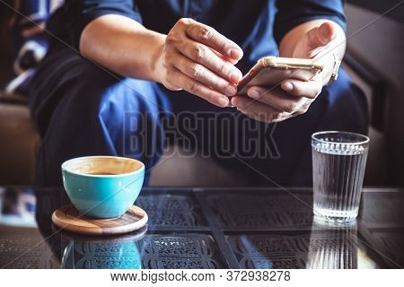 Businessman Using Smartphone To Read Investment News And Reply Email To Confirm Meeting In Coffee Sh