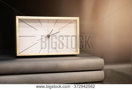 Modern Gold Square Clock On The Pile Of Books On The Wooden Backdrop For Show The Timing Of Life And