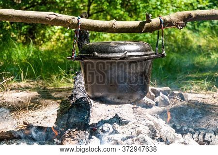 Cooking Food In Bowler Hat With Cover Over Campfire In The Wood. Spurts Of Flame And Haze. The Bowle