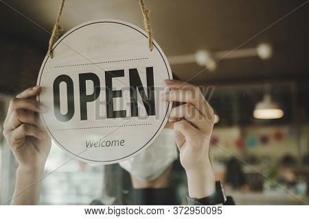Open. Barista, Waitress Woman Wearing Protection Face Mask Turning Open Sign Board On Glass Door In