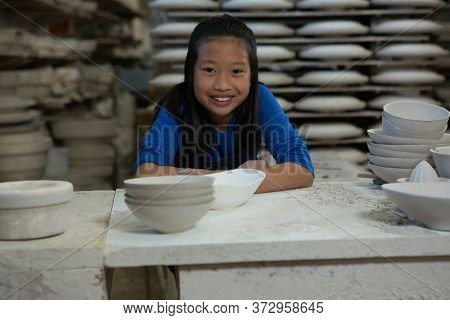 Portrait of happy girl sitting at worktop in pottery workshop