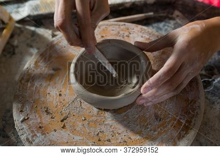 Hands of female potter molding a bowl with hand tool in potter workshop