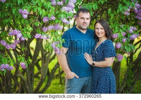 A Beautiful Couple, Husband And Wife Are Standing In A Summer Park Near The Lilac Bushes, They Are H