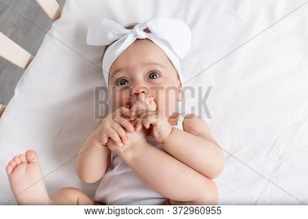 Baby Girl 6 Months Old Lies In A Crib In The Nursery With White Clothes On Her Back And Laughs, Look