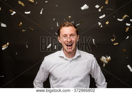 Festive Portrait. Fun Celebration. Amused Man Smiling In Confetti Rain Isolated On Black Background.