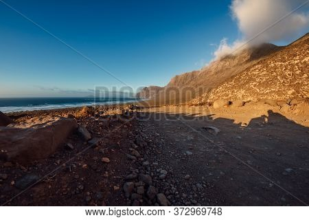 Famara Beach With Dirty Road And Mountains In Lanzarote, Canary Islands