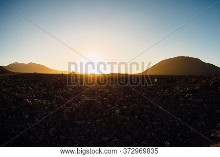 Volcanic Landscape With Volcanos, Dirty Road And Rocks With Sunset Tones At Lanzarote