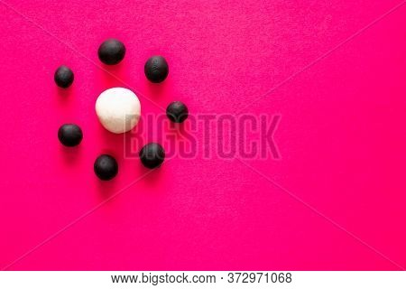 Small Black Balls Surrounding A Large White Plasticine Ball On Pink Vibrant Background. Concepts Of