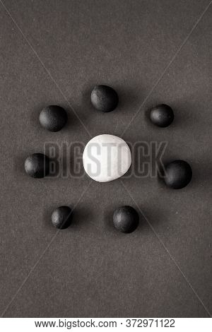 Small Black Plasticine Balls Surrounding A Larger White One. Concepts Of Oppression And Racism, Dive