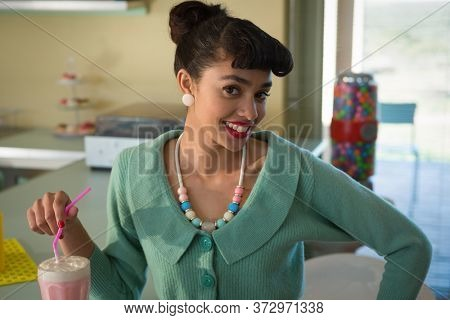 Portrait of smiling woman holding drinking straw looking into camera at restaurant