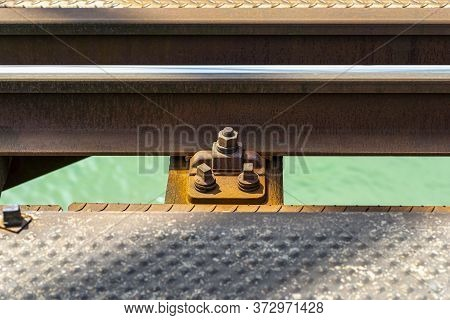 Railroad Tracks Located On The Railroad Bridge Over The River, Close-up On The Fastening Screw, Lyin