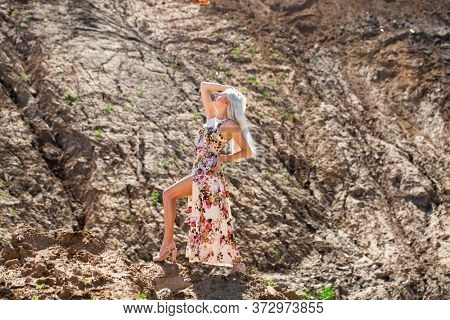 Full body portrait of a young beautiful blonde girl in long dress