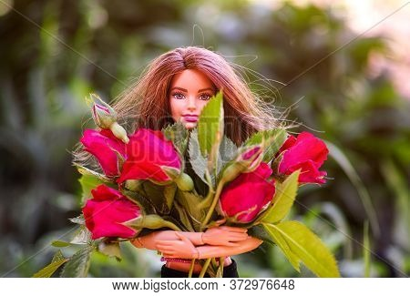Tambov, Russian Federation - June 12, 2020 Brunette Barbie Doll With Big Bouquet Of Red Roses Outdoo