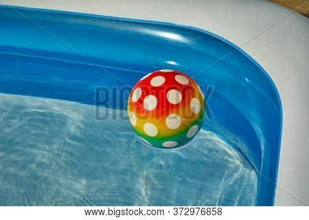 Ball in a garden inflatable pool in summer sunshine, plastic ball with spots, spotted