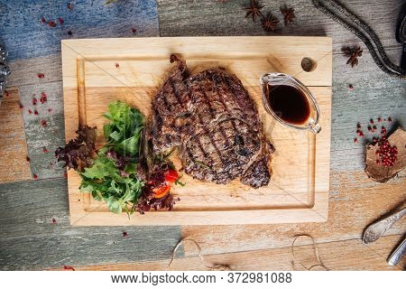 Top View On Juicy Cooked Ribeye Steak With Sauce And Salad On A Wooden Board, Horizontal