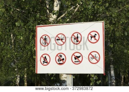 Many Prohibition Signs On One Poster In A Summer Park. Do Not Litter, Do Not Smoke, Do Not Drink Alc