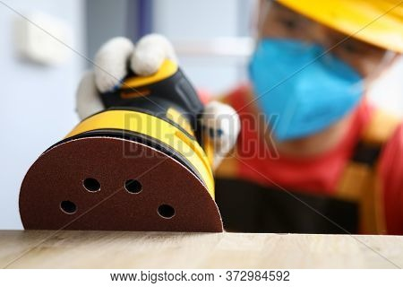 Masked Carpenter Grinds Wood With Sander Machine. Tool Is Used For Polishing And Grinding Surfaces W