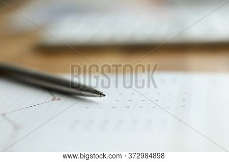 Close-up Of Business Paper Laying On Desktop With Silver Pen. Graph And Diagram With Numbers. Income