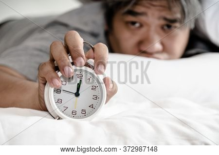 Asian Middle Aged Man Just Waking Up Looking At The Alarm Clock Held In The Hand, On White Bed In Th