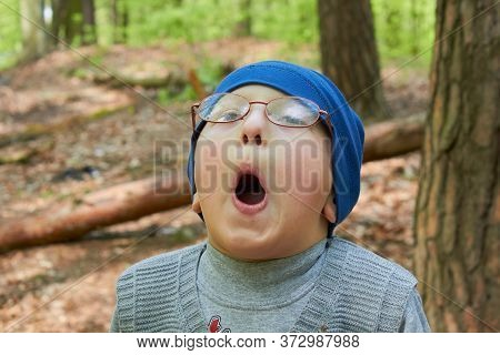 Boy Opened His Mouth In The Forest, In Autumn A Boy In Glasses In The Woods With His Mouth Open Sing