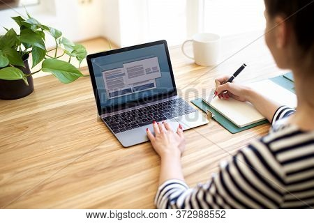 Cropped Shot Of Businesswoman Typing On Laptop's Keyboard And Makig Notes. Unrecognizable Woman Sitt