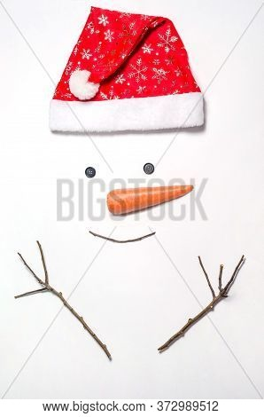 Snowman's Face On A White Background. A Set Of Items For Making A Snowman - A Red Hat, Carrots, Eyes