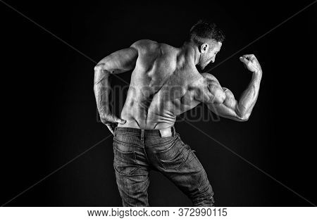 Create Your Power. Athletic Trainer Black Background. Athletic Man Show Biceps Triceps. Sexy Sportsm