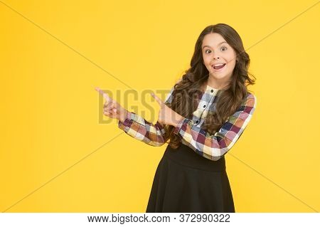 Check It Out. Happy Girl Pointing At Yellow Background Copy Space. Little Kid With Pointing Gesture.