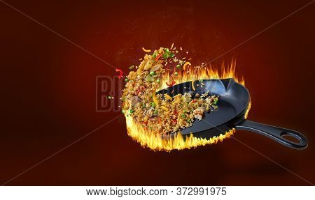 Delicious Chinese Fried Rice Being Stir Fried In Hot Flaming Pan And Tossed In Midair With Chicken,