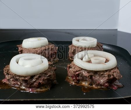 Frying Four Venison Burgers Garnished With Onion Rings, In Non-stick Fry Pan On Top Of An Electric S