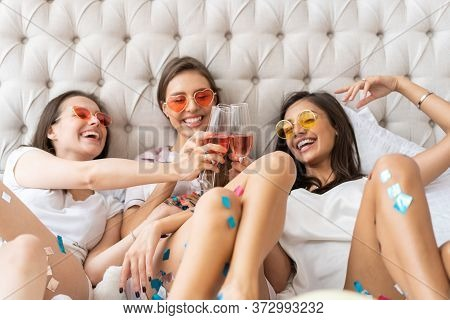 Pajama Party. Attractive Young Smiling Women In Pajamas Drinking Champagne While Having A Slumber Pa