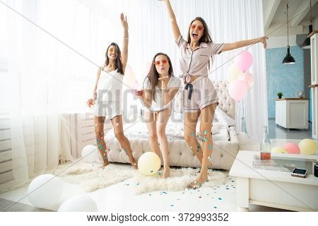 Three Attractive Young Women In Pajamas Smiling And Gesturing While Jumping In Bedroom With Confetti