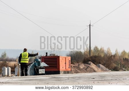 Lviv, Ukraine - October 23, 2019: Back View Of Worker Starting Engine Of Generator During Roadworks