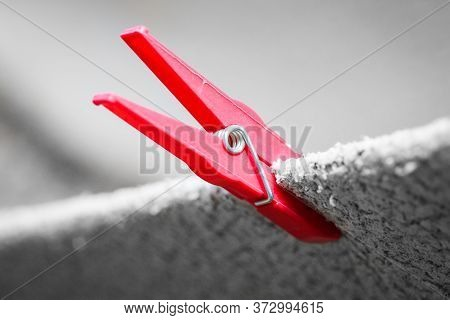 Red Clothes Peg Holding Washed Bright Blanket