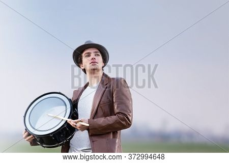 Drummer guy holding and playing single drum outdoors. Hipster young man with one drumstick and percussion instrument performing indie funk music