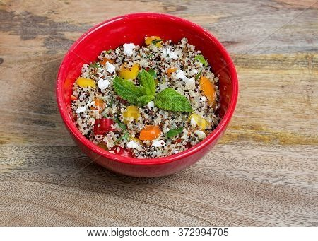 Closeup On Red Bowl With Tri-color Quinoa Salad On Wooden Background - Quinoa Is A Pseudograin That