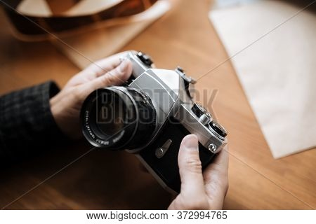 Vintage Pentax Film Camera In The Hands Of A Man On A White Background. Horizontal. Top View
