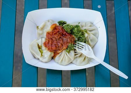 Closeup On Vegie Indian Momos  - Steamed Dumplings With Tomato And Cilantro Sauce.- Served In A Carr