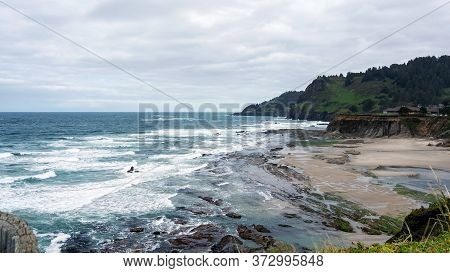 Landscape Of An Oregon Beach Between Coss Bay And Charleston, Featuring Rocks And A Cloudy Sky