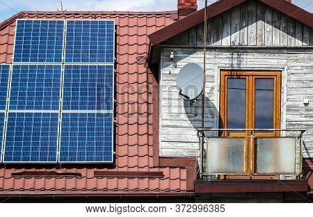 Solar Panels On The Roof Of Old Wooden House With Attic And Small Balcony