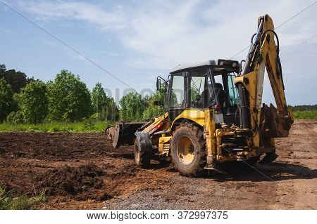 Clearing And Leveling A Private Land Plot. Yellow Excavator Driven Earth In A Wide Bucket, Back View