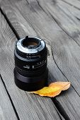 Camera lense and autumn leaf on old wood poster