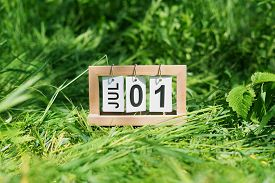 Folding Calendar With The Date Of July 1 St On A Grassy Lawn.