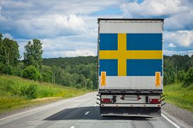 A  Truck With The National Flag Of Sweden Depicted On The Back Door Carries Goods To Another Country