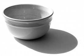 White Bowl. White Ceramic Bowl. Artistic view of a white ceramic bowl with shadows. Isolated on white. Room for text. Clipping Path. Bowls are used world wide for Soups and other liquid ingredients.