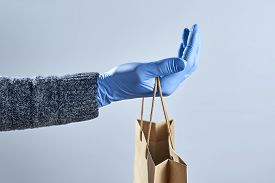 A Hand In A Blue Medical Glove Holds Out A Paper Bag On A Gray Background. Concept Of Safe Delivery.