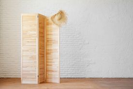 Louvered Wooden Screen With A Straw Hat On A Background Of A White Brick Wall With Copy Space. Trave