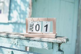 Folding Calendar With The Date Of July 1st On The Old Ragged Railing. Porch Of A Shabby Country Hous